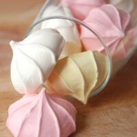 Meringue kisses in a glass jar falling over with meringue cookies falling out.