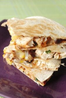 Chicken and pineapple stuffed quesadillas stacked on a purple plate.