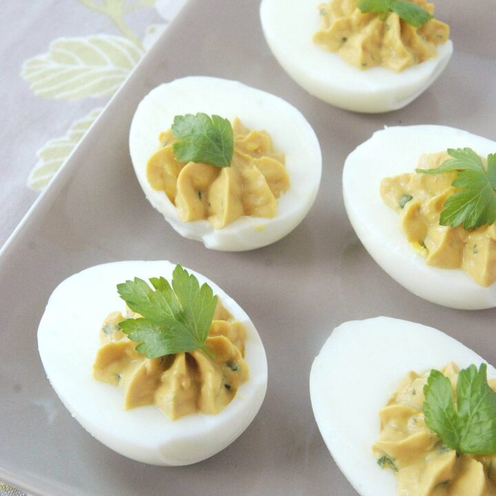 Five deviled eggs topped with a parsley leaf on a grey plate