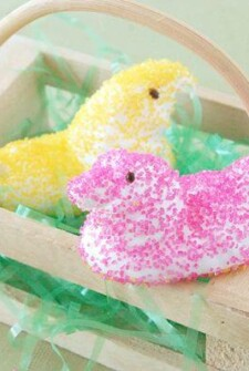 Two marshmallow treats shaped like birds in a wooden basket