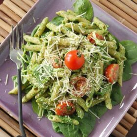 Spinach pesto pasta with tomatoes on a square purple plate