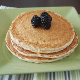 Stack of three pancakes topped with three blackberries on a green plate