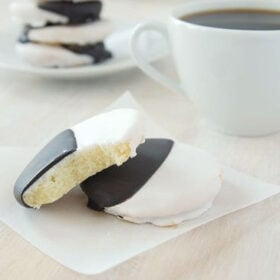 black and white cookies stacked on top of each other with a white plate and a cup of coffee