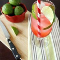 Cherry limeade drink on a napkin on a cutting board with limes in a bowl and a knife