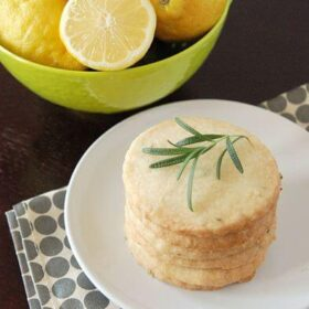 Stack of shortbread cookies on white plate next to bowl of lemons