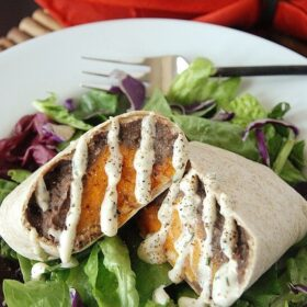 Sweet potato black bean burrito cut in half on a salad
