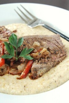 A Shallow White Bowl Containing Cheese Grits, Stuffed Flank Steak and a Fork