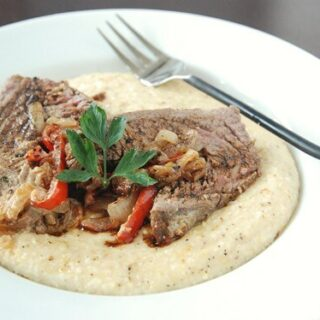 Grits in a shallow bowl with stuffed flank steak on top and a fork