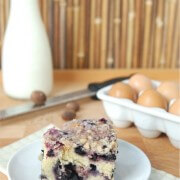 Blueberry buckle on a white plate with eggs, milk and nutmeg in background.