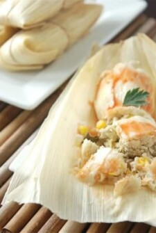 White plates with tamales on them cut into pieces with a fork.