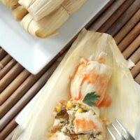 Overhead image of wrapped tamales and one tamale unwrapped.