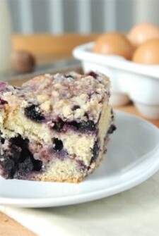 A slice of blueberry buckle on a white plate.