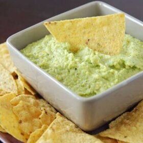 Bowl of brocamole dip with a chip in the center and around the bowl.