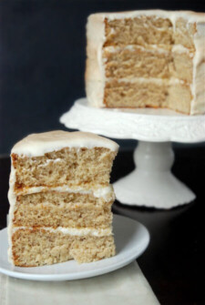 Three layers of banana cake with a slice on a plate and the cake on a cake stand.