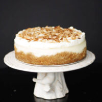 Coconut cheesecake on a white cake stand with toasted coconut on top.
