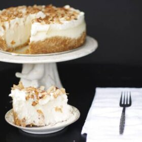 Slice of coconut cheesecake on a plate in front of whole cheesecake on a cake stand with a white napkin and fork