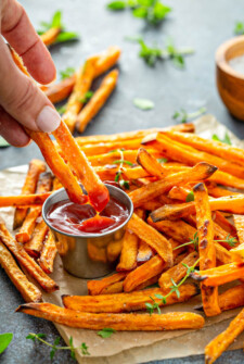 Sweet potato fries on parchment paper being dipped into ketchup.