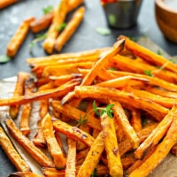 Sweet potato fries on parchment paper with herbs on top.
