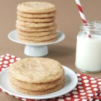 Three snickerdoodle cookies on a white plate with a glass of milk and a red napkin.