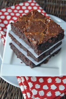 Three brownies stacked on top of each other on a white plate with a red napkin.