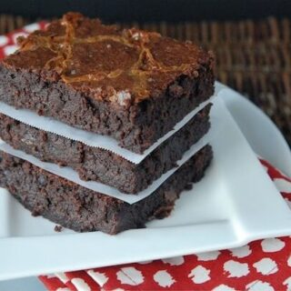 Three brownies stacked on top of each other with a white plate and a red napkin.