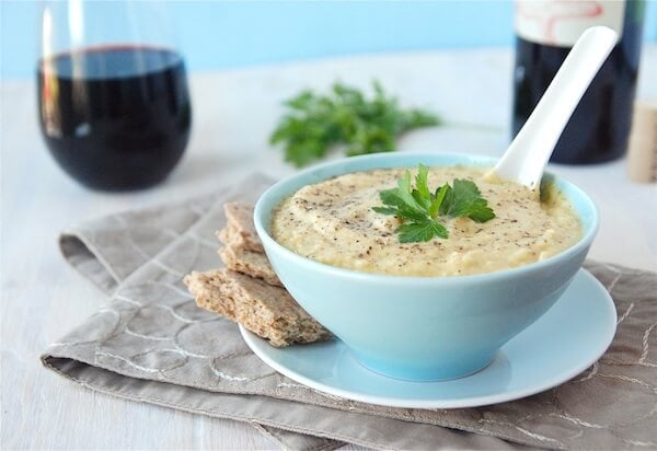 Roasted Garlic Cauliflower Soup in a blue bowl with a glass of wine