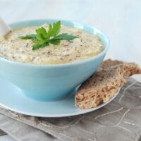 Roasted Garlic Cauliflower Soup in a blue bowl with a piece of bread