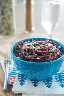 Bowl of Red Wine Spaghetti with parmesan cheese in a blue bowl