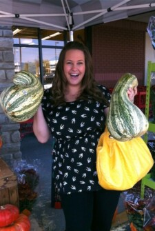 Girl holding two stripe cushaw squash out side of a grocery store.