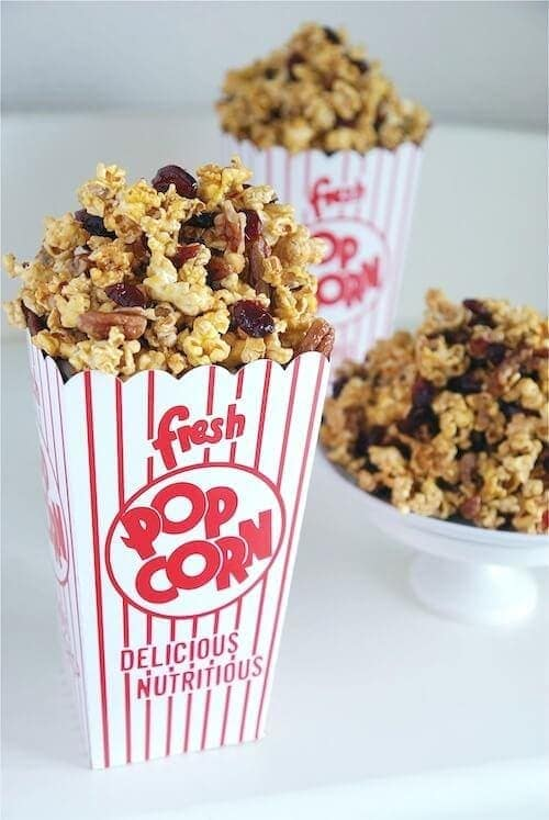 A popcorn container and a bowl filled with Cranberry Orange Caramel Corn