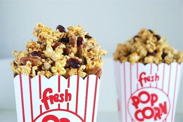 Caramel popcorn with nuts and cranberries in two popcorn containers