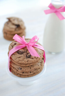 Triple Chocolate Malt Cookies stacked and tied with a pink bow and a jar of milk in the background