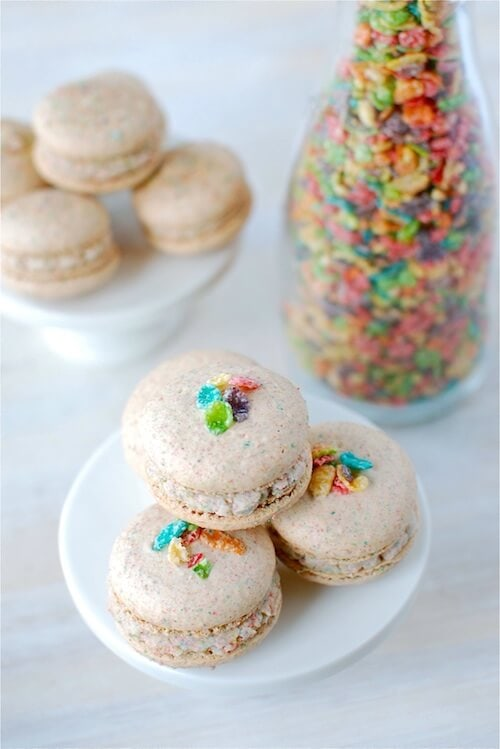 A Stack of Fruity Pebble Macarons on a White Stand with Another Stand and a Jar of Cereal in the Background