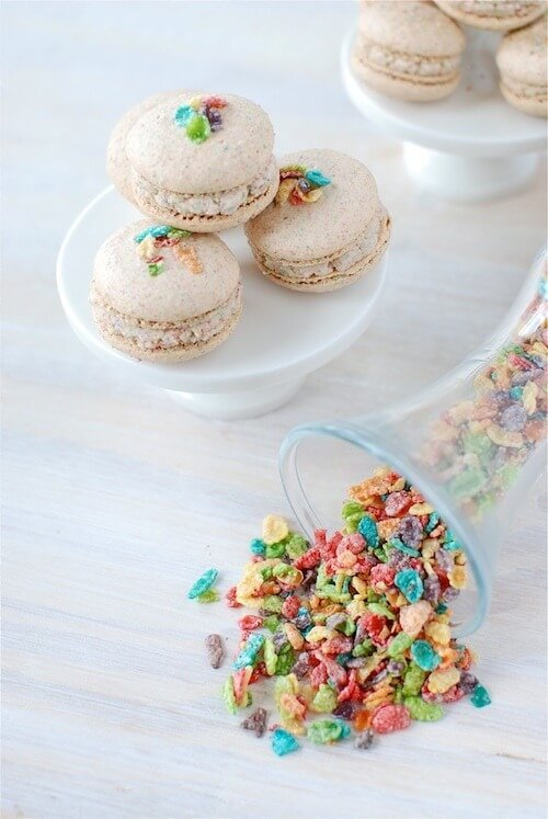 Four Macarons on a Cupcake Stand Beside Loose Fruity Pebbles Cereal on a Pale Wooden Table