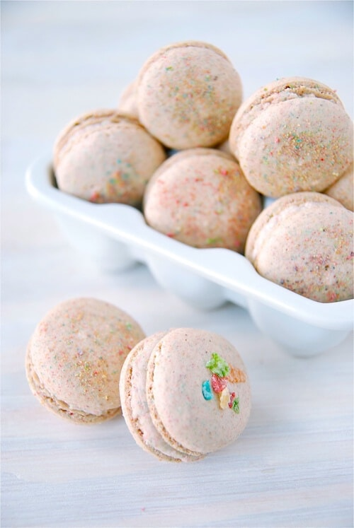 A White Container of Fruity Pebble Macarons with Two Macarons in the Foreground