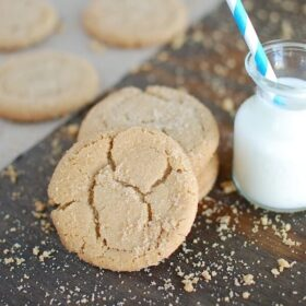 Brown butter brown sugar cookies set near a glass of milk with a blue and white straw. More cookies are in the background.