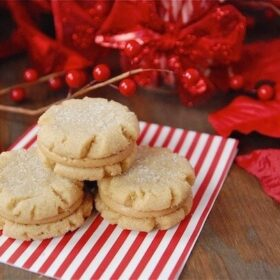 Peanut Butter Creamwiches on a red and white striped napkin, with red berried and red poinsettas