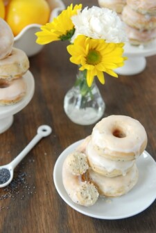 Stacks of Lemon Poppy Seed Donuts on a white plate with a small arrangement of yellow and white flowers