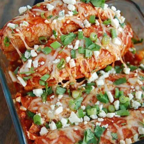 buffalo chicken enchiladas with green onions and blue cheese on top with a spatula pulling out enchiladas
