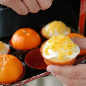 Clementine muffins in a muffin pan with white icing and orange sprinkles and oranges.