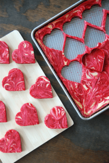 Red velvet brownies with cream cheese swirled through them in a baking pan being cut into hearts.