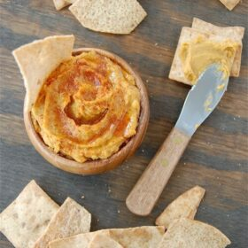 Overhead image of sweet potato hummus in a bowl with pita chips and a spreader knife.