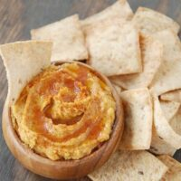 Sweet potato hummus with olive oil drizzled on top in a bowl with pita chips.