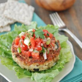 Tuna cake on a piece of lettuce on a plate with salsa on top.