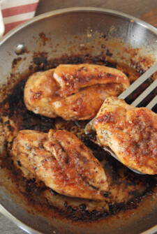Three Pan-Seared Garlic Butter Brown Sugar Chicken Breasts in a Metal Skillet on a Table