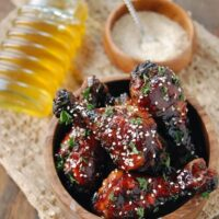 Drumsticks covered in sauce and sesame seeds.