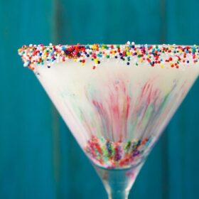 Up close image of cake batter martini with rainbow sprinkles inside and on rim