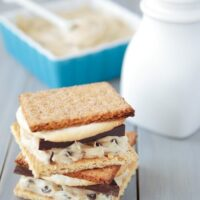 Delicious cookie dough s'mores stacked on top of each other with a white ceramic milk container