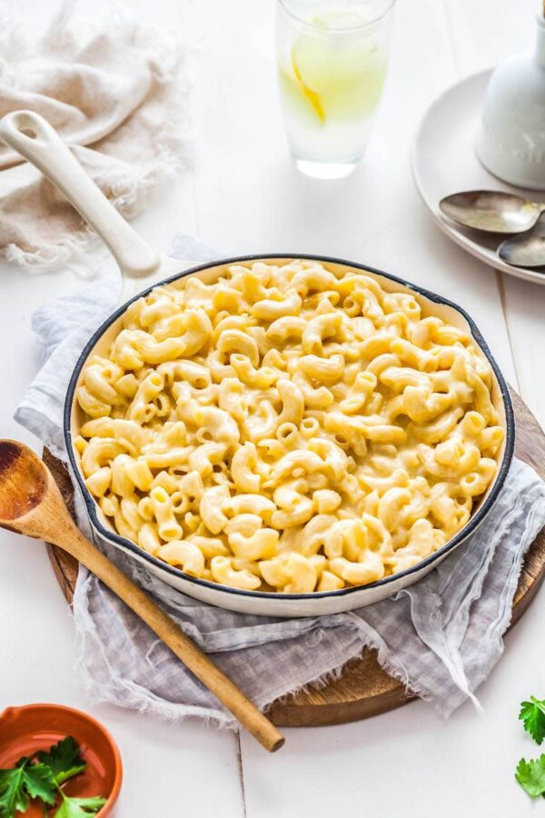 Mac and Cheese in a large skillet with a wooden spoon