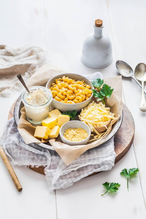A platter with sour cream, cheese, butter, cream cheese and noodles.